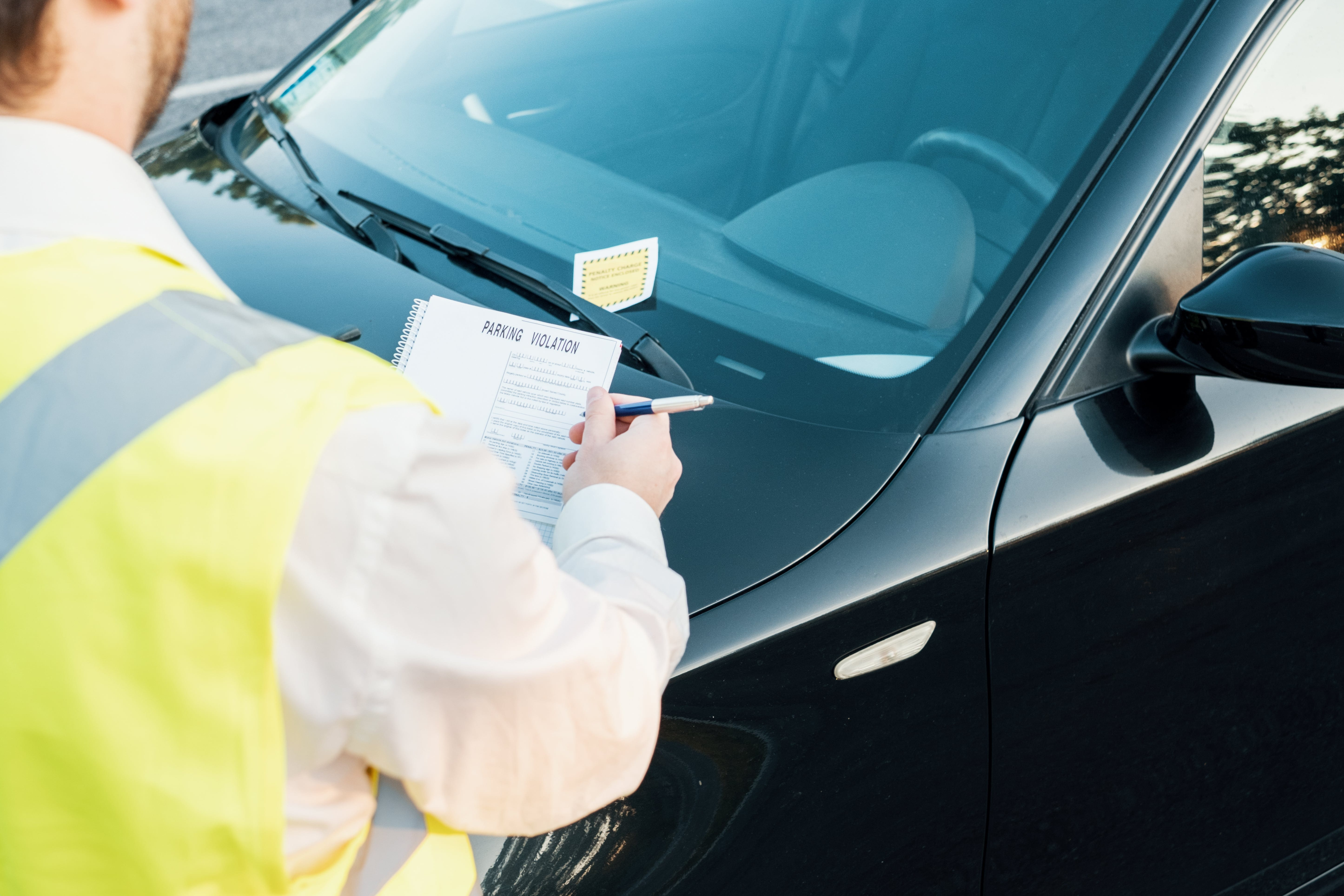 Flex Point Security guard writing a parking infraction notice as he is licensed as a Contract Certified Officer