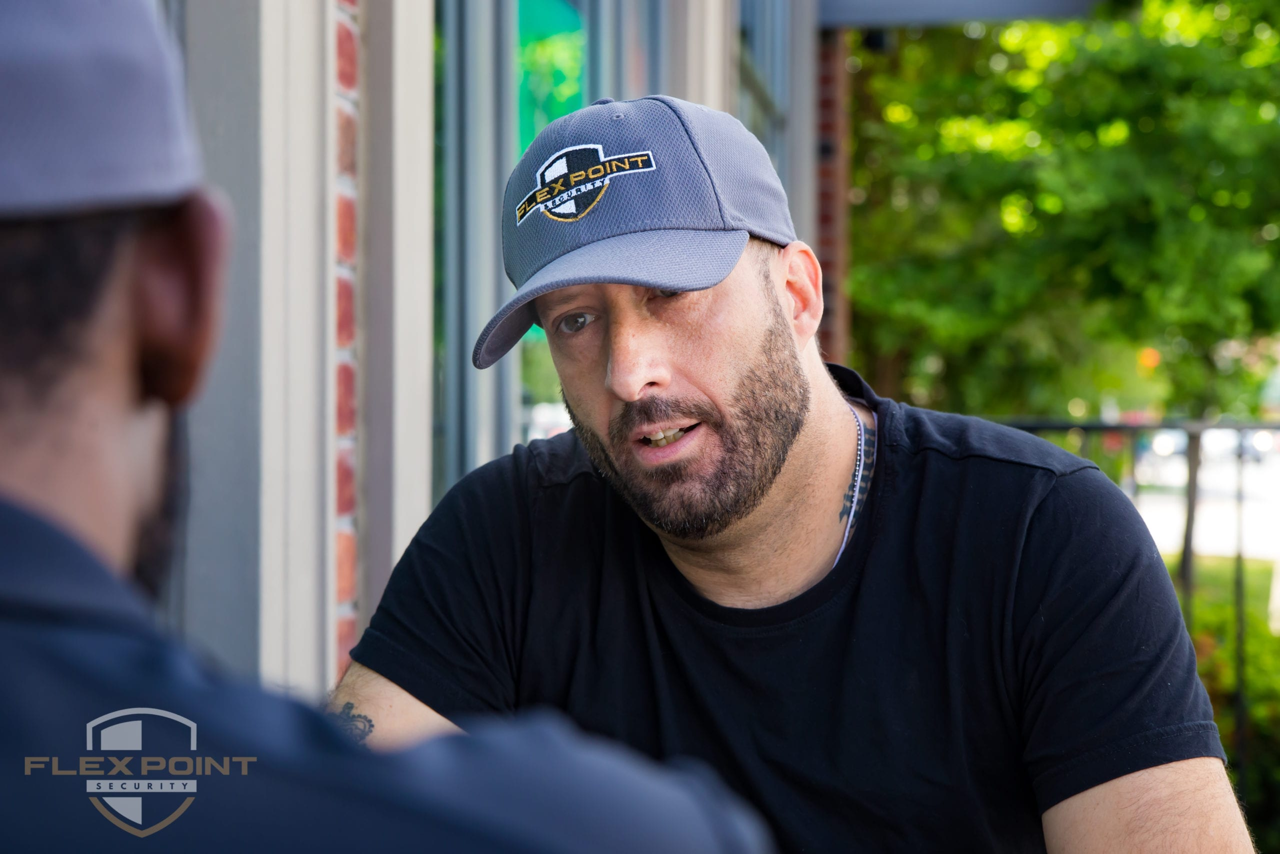 Two Flex Point Security guards wearing branded hats outside of a residence having a discussion