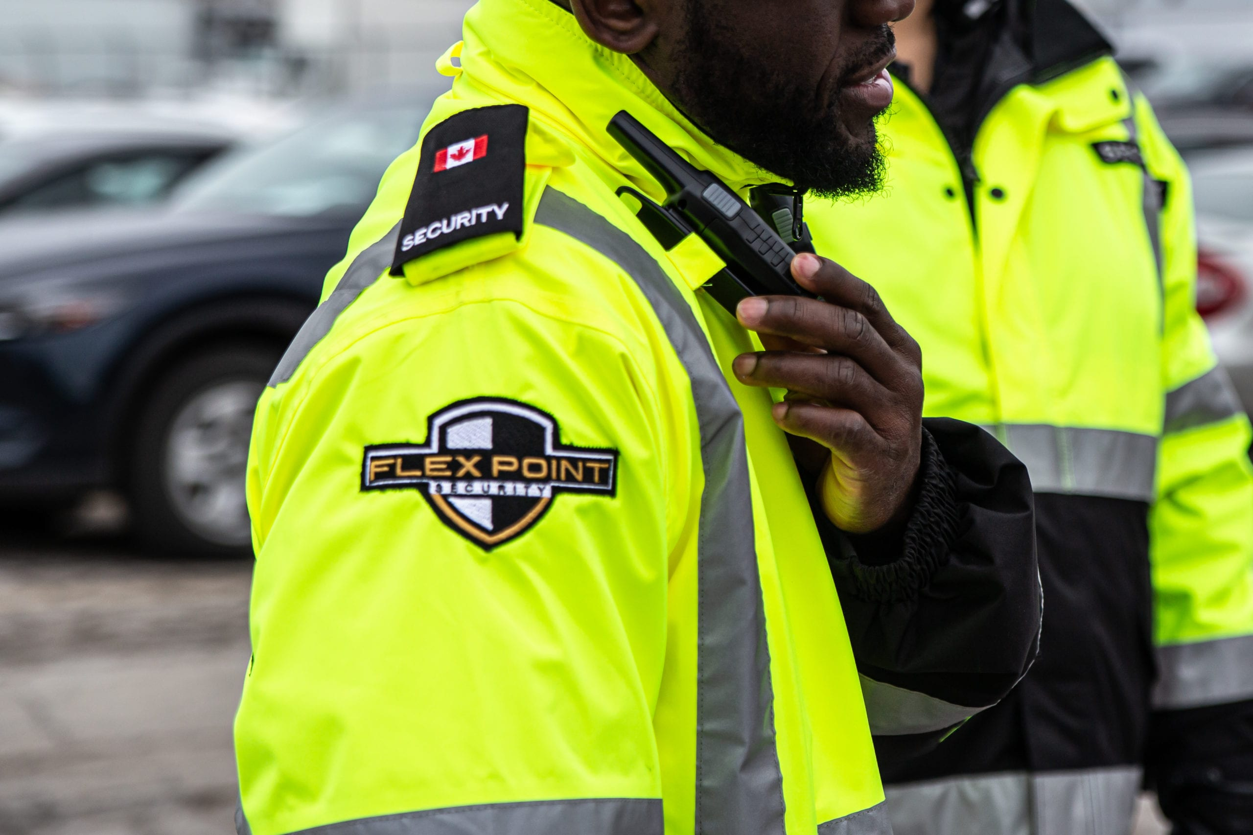 Two Flex Point Security guards standing in a parking lot in branded yellow jackets