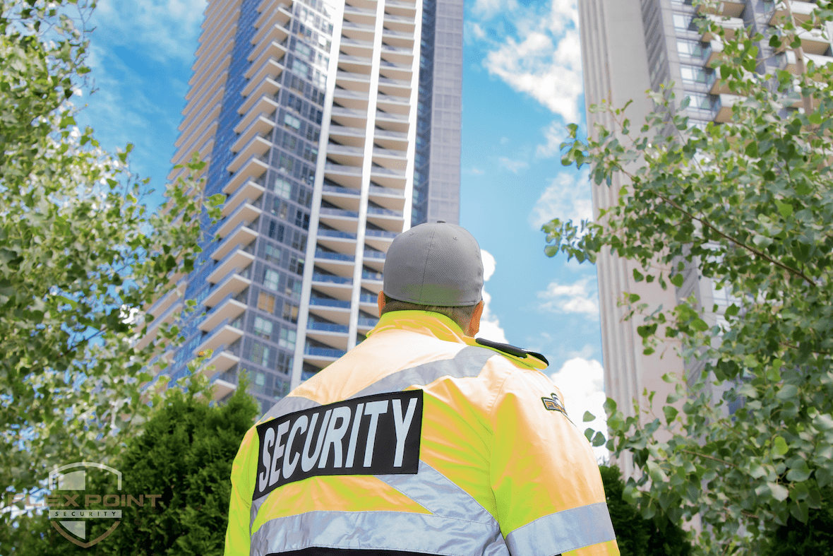 Flex Point Security guard looking up at two condos where he provides residential security services