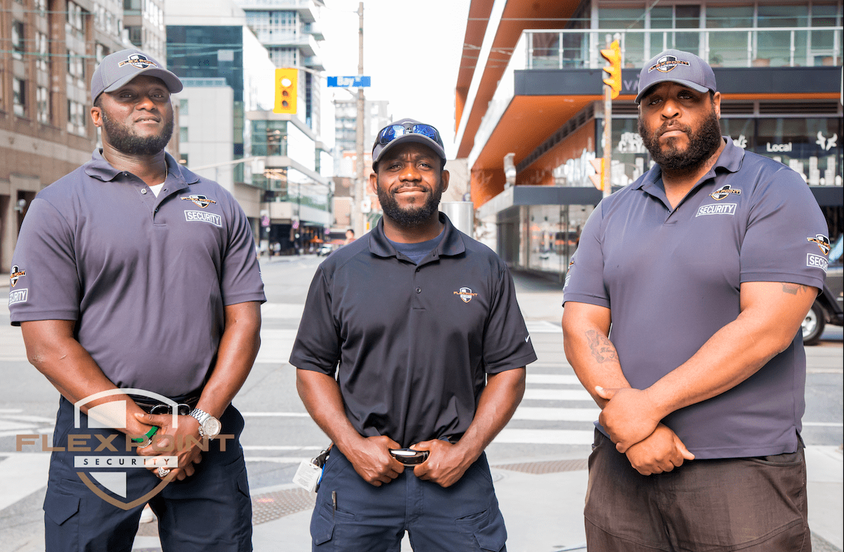 Three Flex Point Security guards wearing branding shirts and hats standing on Bay St. in Downtown, Toronto