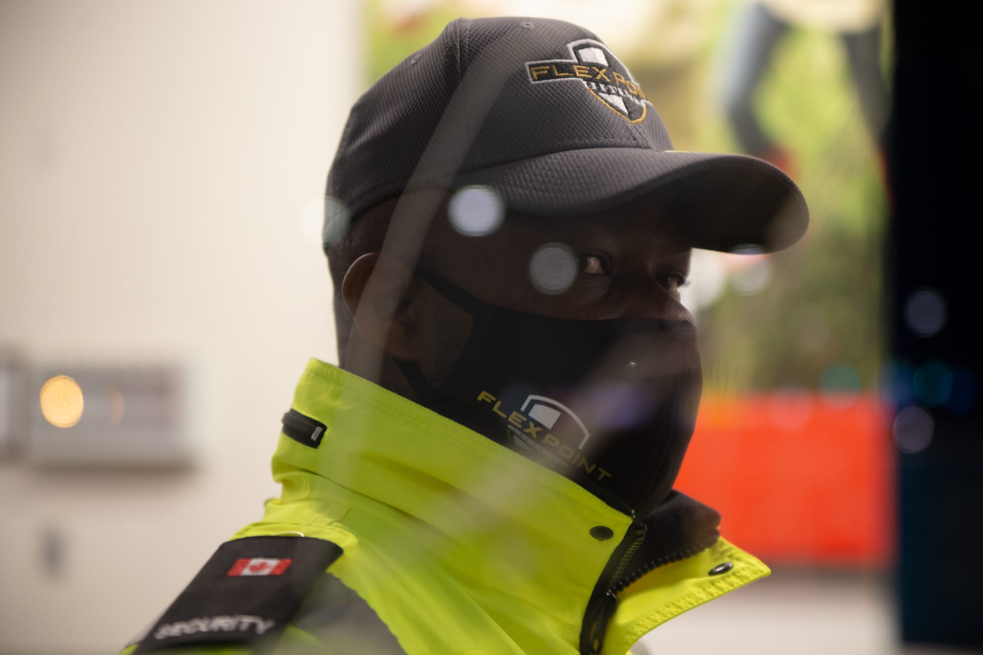 Flex Point Security guard at a commercial building wearing a branded hat, face mask and jacket standing with a blurred background