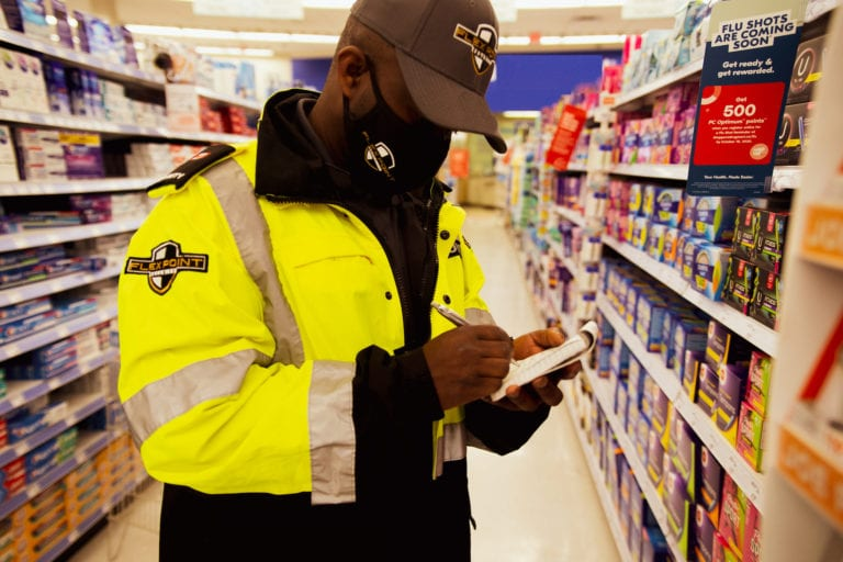 Flex Point Security guard writing on a notepad as he provides loss prevention security services at a retail store