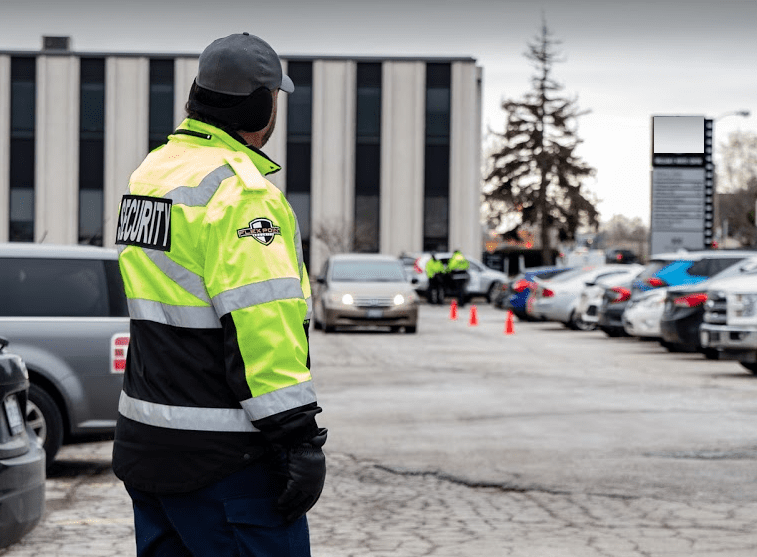 Flex Point Security guard wearing a branded jacket providing parking enforcement services at a commercial property in the Greater Toronto Area