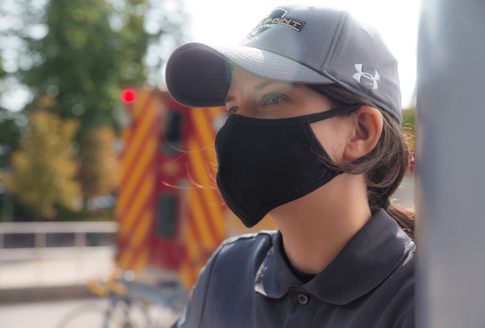 Female Flex Point Security guard at a commercial property wearing a branded hat and face mask