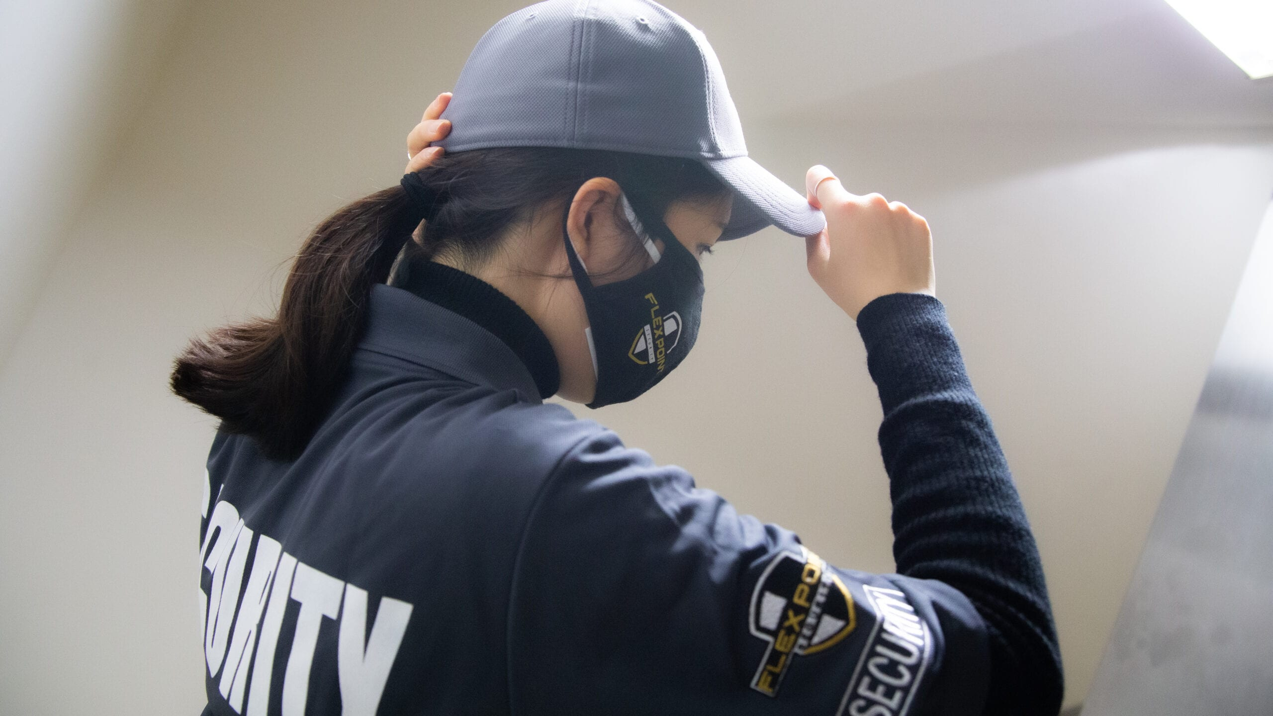 Female Flex Point Security guard with branded clothing on adjusting her hat