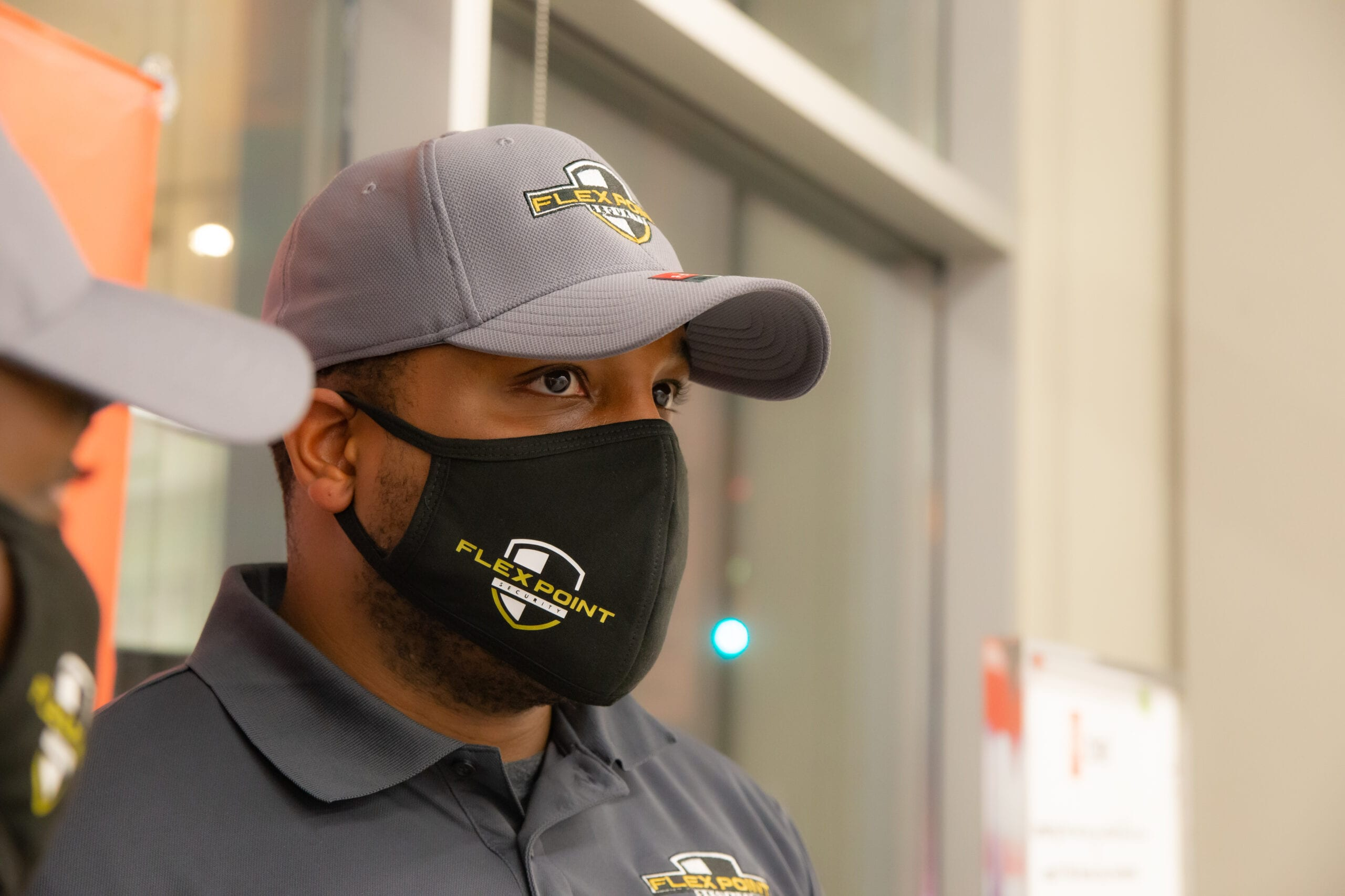 Close up of a Flex Point Security guard providing office building security while wearing a branded face mask, hat, and t-shirt.