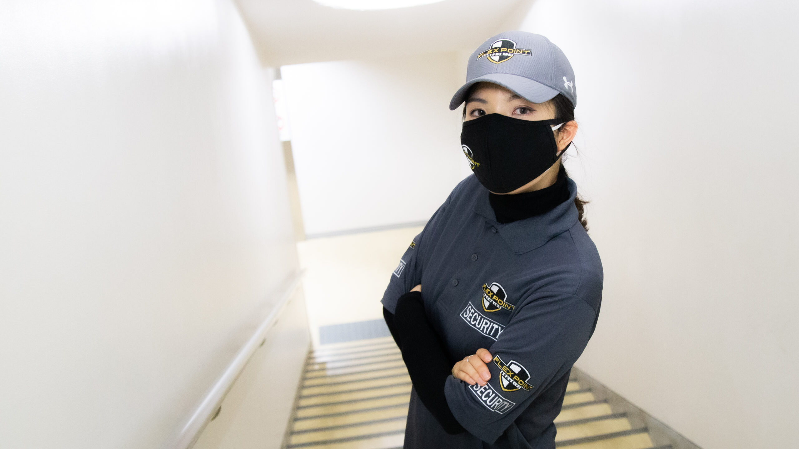 Female Flex Point Security guard standing in a stairwell as she provides office building security