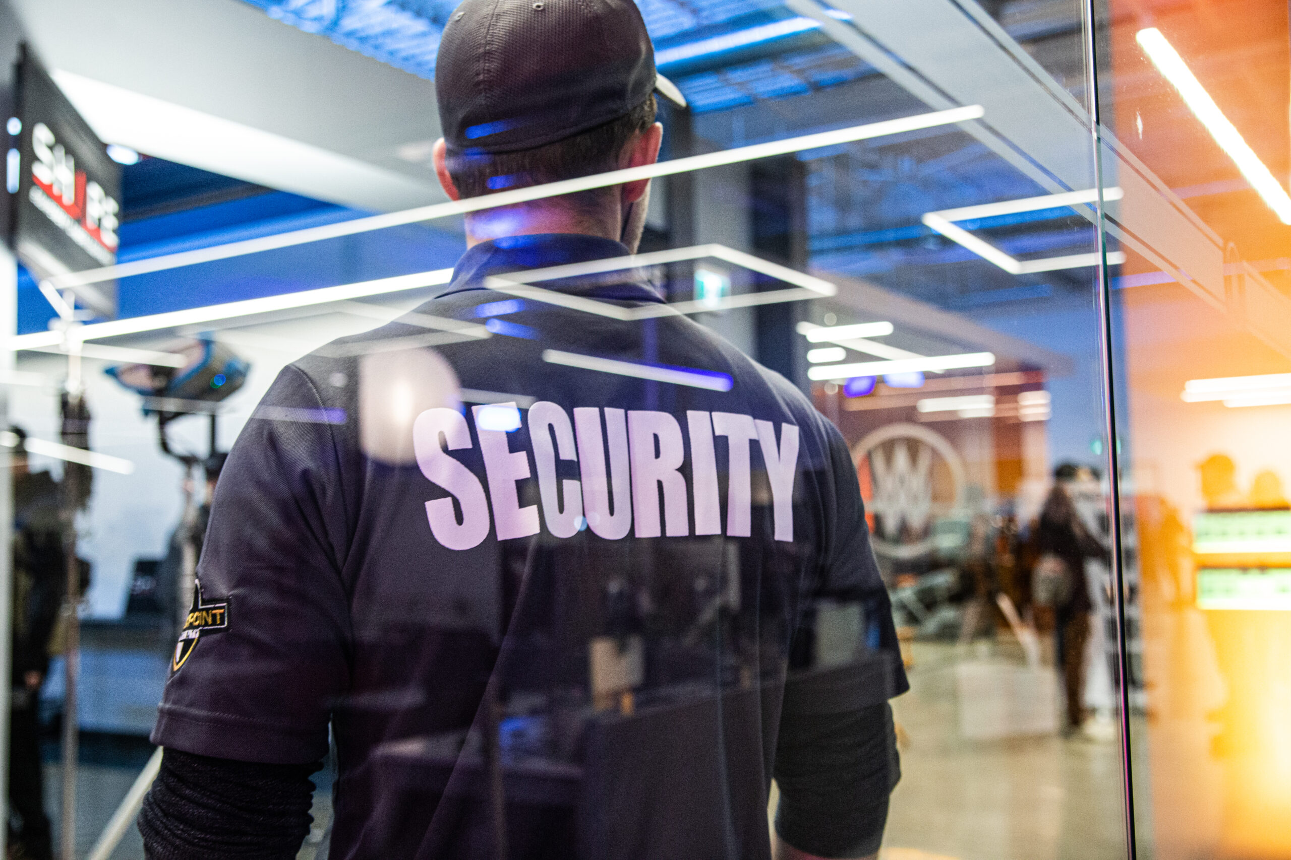 Flex Point Security guard standing next to a commerical office building's glass wall as he provided office building security