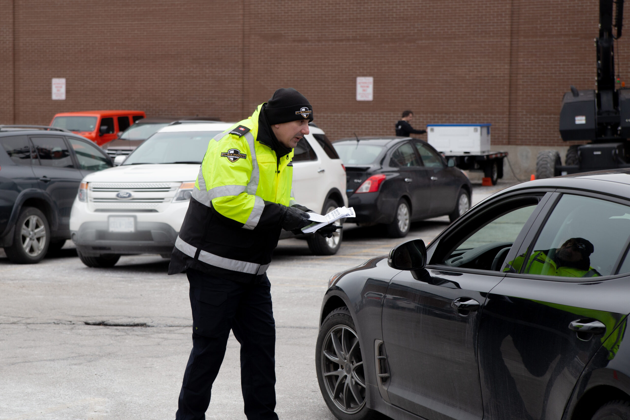 Male Flex Point Security guard providing traffic control services and speaking to a driver in a vehicle