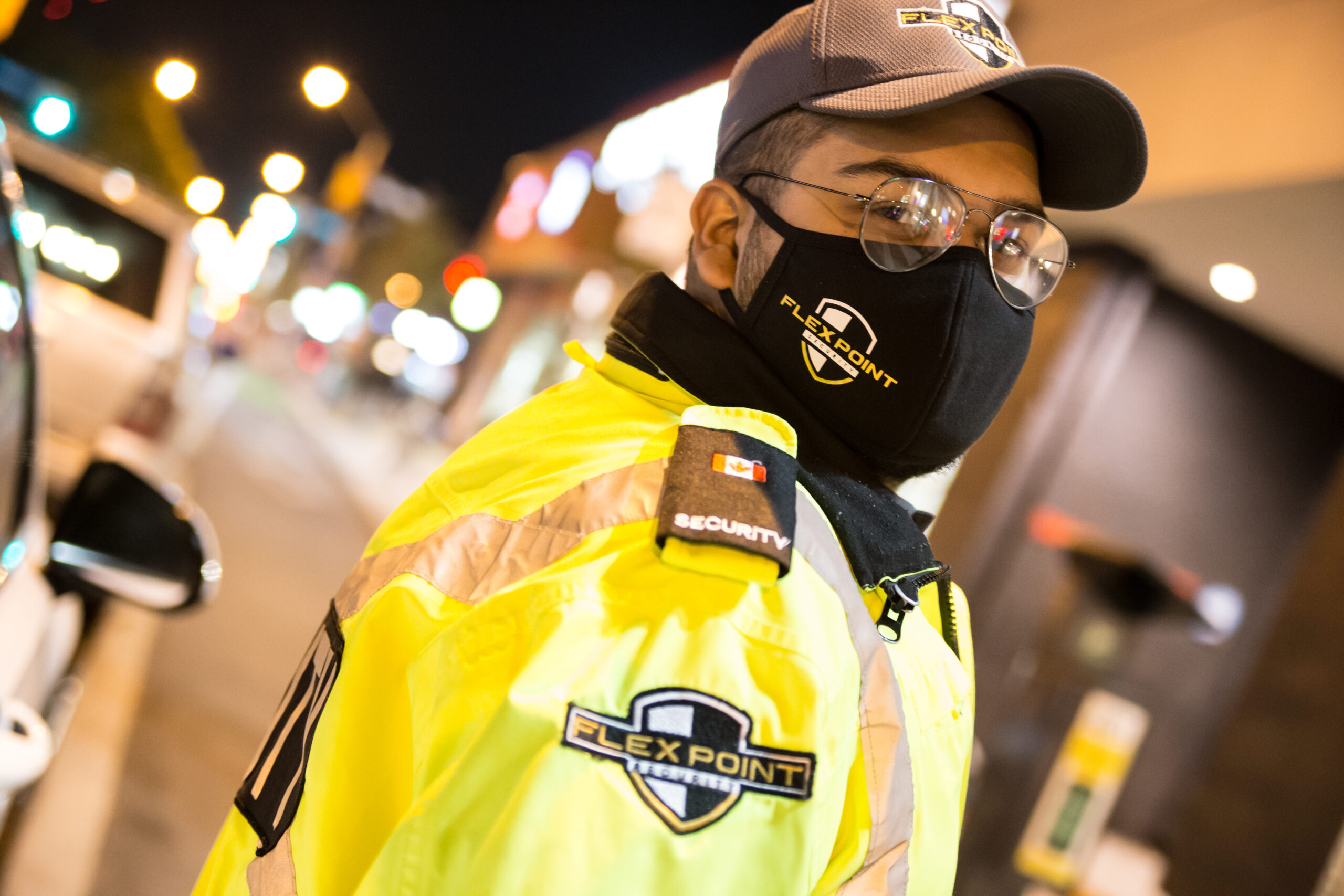 Male Flex Point Security guard wearing a branded hat, face mask and jacket while standing next to a company security vehicle in Toronto
