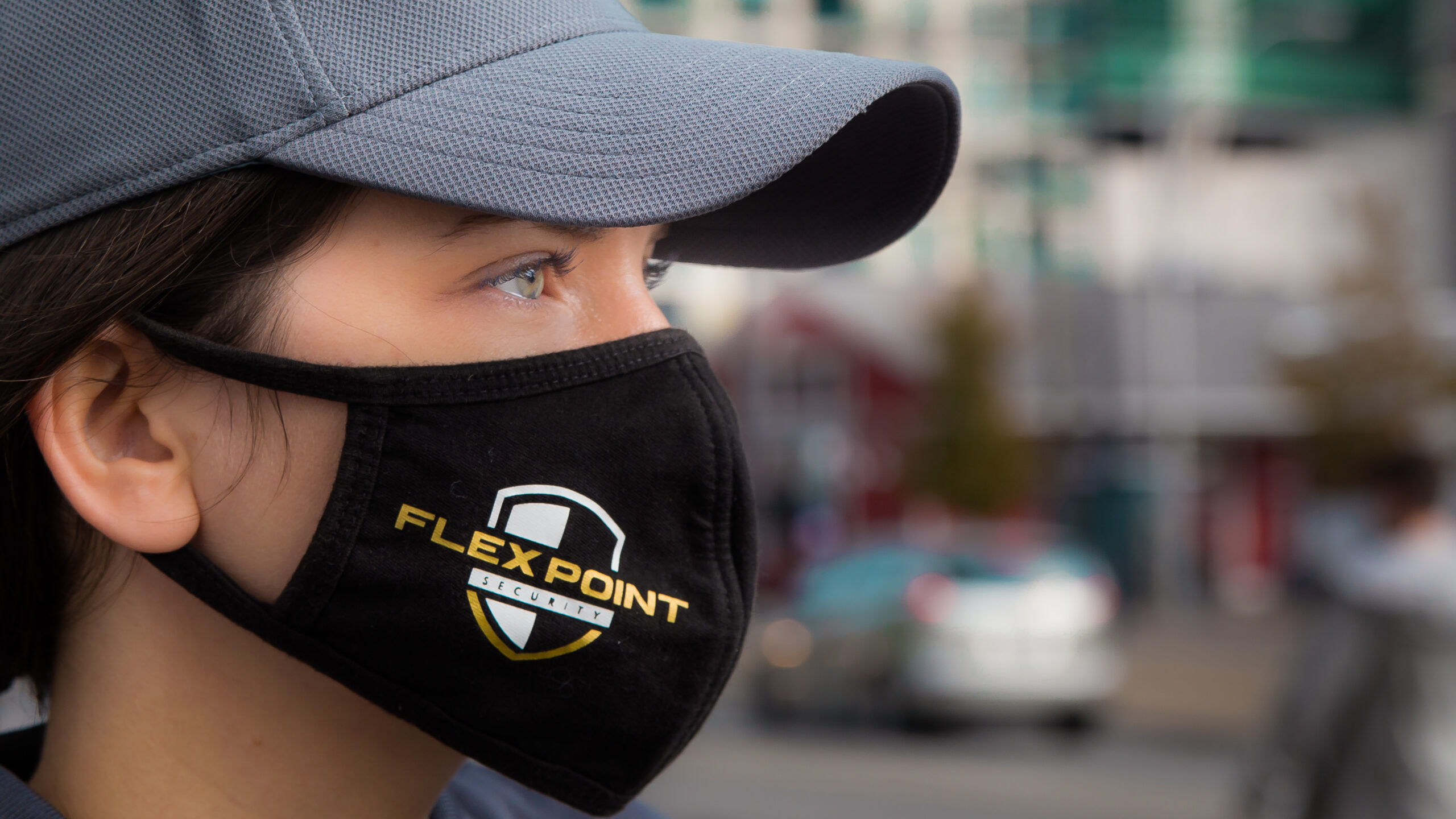 Close up of a female Flex Point Security guard's face as she wears a branded hat and face mask