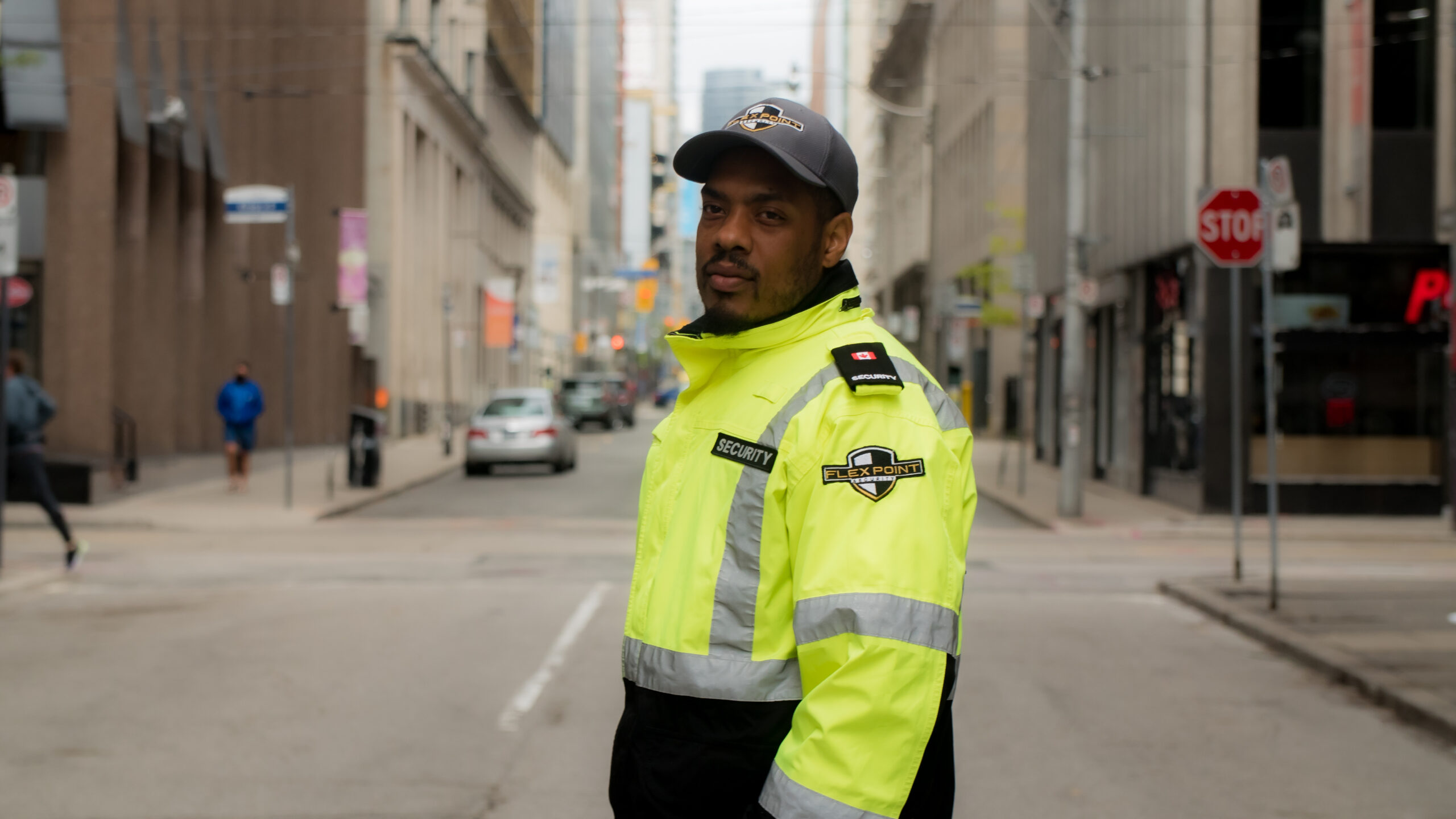 Male Flex Point Security guard providing traffic control services and standing on the street in Downtown, Toronto